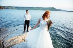 Beautiful gorgeous blonde bride and stylish groom on rocks Stock Photo