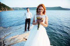 Beautiful gorgeous blonde bride and stylish groom on rocks Stock Images