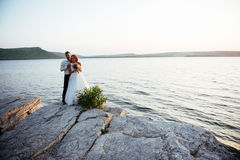 Beautiful gorgeous blonde bride and stylish groom on rocks Royalty Free Stock Images