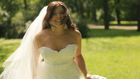 Beautiful gorgeous bride in exellent white dress with long veil playfully runs away on lawn in the park stock video footage
