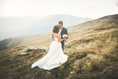 Beautiful gorgeous bride posing to groom and having fun, luxury ceremony at mountains with amazing view, space for text. Wedding couple Royalty Free Stock Image