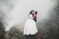 Beautiful gorgeous bride posing to groom and having fun, luxury ceremony at mountains with amazing view, space for text. Wedding couple Stock Photos