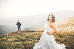 Beautiful gorgeous bride posing to groom and having fun, luxury ceremony at mountains with amazing view, space for text. Wedding couple Royalty Free Stock Photo