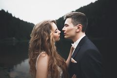 Beautiful gorgeous bride posing to groom and having fun, luxury ceremony at mountains with amazing view, space for text. Wedding couple Royalty Free Stock Photography