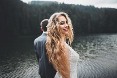 Beautiful gorgeous bride posing to groom and having fun, luxury ceremony at mountains with amazing view, space for text. Wedding couple Stock Photography