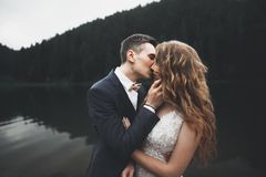 Beautiful gorgeous bride posing to groom and having fun, luxury ceremony at mountains with amazing view, space for text. Wedding couple Stock Photo