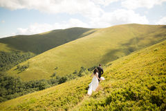 Beautiful gorgeous bride posing to groom and having fun, luxury ceremony at mountains with amazing view, space for text Royalty Free Stock Photos