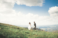 Beautiful gorgeous bride posing to groom and having fun, luxury ceremony at mountains with amazing view, space for text Royalty Free Stock Image