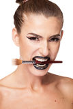 Beautiful gorgeous brunette woman holding a makeup brush in mout Royalty Free Stock Photos