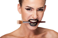 Beautiful gorgeous brunette woman holding a makeup brush in mout Royalty Free Stock Photo