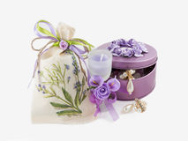 Beautiful gorgeous golden earings in violet gemstone box,  aroma candle and linen stack Royalty Free Stock Photo