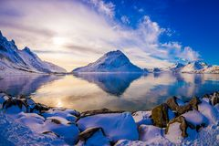 Beautiful gorgeous scenic view of mountain reflecting in the lake in Svolvaer, with rocks covered with snow Stock Image