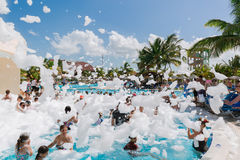 Beautiful, gorgeous view of happy smiling joyful people relaxing and enjoying their time in swimming pool foam party on sunny day Royalty Free Stock Photography