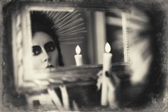 Beautiful goth girl holding candle in hand and looking into mirror. Grunge texture effect. Beautiful goth girl holding candle in hand and looking into the mirror Royalty Free Stock Photo