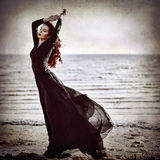 Beautiful goth girl standing on sea coast. Grunge texture effect Royalty Free Stock Images