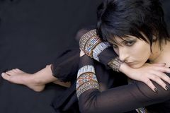 Beautiful Goth Woman Sitting. Beautiful goth woman with green eyes and black fingernails sitting, leaning chin on hand Royalty Free Stock Photography