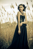 Beautiful gothic. Beautiful brunette woman wearing long black dress and black headwear posing among the reeds. The old times, the Gothic style. Fashion stock images