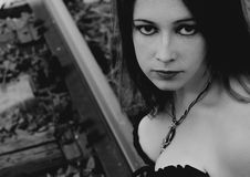 Beautiful gothic girl is sitting on rails Royalty Free Stock Photography