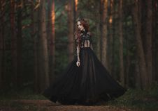 A beautiful gothic princess with pale skin and very long red hair in a black crown and a black long dress in a misty fairy forest. stock photography