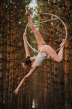 Beautiful and graceful aerial gymnast does exercises on the ring. In the forest Stock Photos