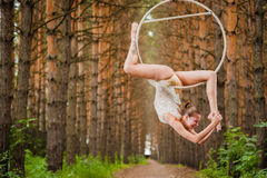 Beautiful and graceful aerial gymnast does exercises on the ring Royalty Free Stock Images
