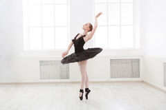 Beautiful graceful ballerina in black swan dress. Young ballet dancer practicing before performance in black tutu, classical dance studio, copy space Stock Photos