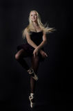 Beautiful graceful blond dancer in bright satin pointe. Royalty Free Stock Image
