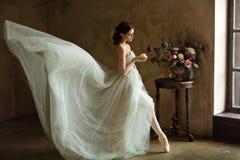 Beautiful graceful girl ballerina in an air dress looking at flo stock photo