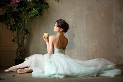 Beautiful graceful girl ballerina in an air dress and pointe sit stock photo