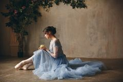 Beautiful graceful girl ballerina in a blue dress and pointe sit royalty free stock photography
