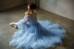 Beautiful graceful girl ballerina in a blue dress and pointe sit stock photography