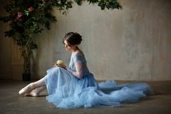 Beautiful graceful girl ballerina in a blue dress and pointe sit royalty free stock image