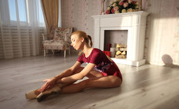 Beautiful graceful young ballerina in pointe shoes on wooden floor makes ballet leg stretching. royalty free stock image