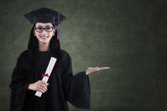 Beautiful graduate holding certificate in class Royalty Free Stock Photos