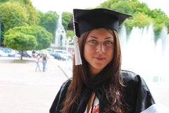 Beautiful graduation girl in cap and gown portrait Royalty Free Stock Photography