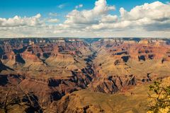 Skyline above the grand canyon. Beautiful Grand Canyon shapes under the sunny sky with shadows falling down from the clouds Royalty Free Stock Photography