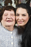Beautiful grandma and granddaughter. Portrait of beautiful grandma and her granddaughter standing with their faces closed each other and smiling in a living room Royalty Free Stock Photography