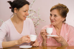 Beautiful grandmother and granddaughter. Drinking tea Stock Photos