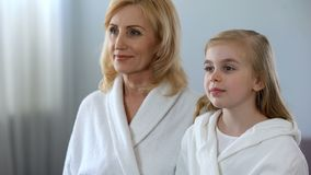 Beautiful grandmother and granddaughter looking at mirror in bathroom, skin care. Stock photo stock photos