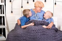 A beautiful grandmother and two grandsons are sitting on the sofa under a knitted merino wool blanket.A happy family. royalty free stock photography