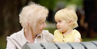 Beautiful granny and her little grandchild together in park stock photos