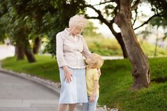 Beautiful granny and her little grandchild walking together in park. Grandma and grandson royalty free stock images