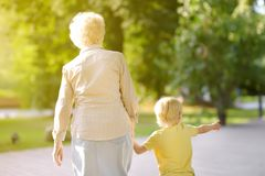Beautiful granny and her little grandchild walking together in park royalty free stock image