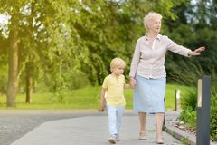 Beautiful granny and her little grandchild walking together in park stock photos