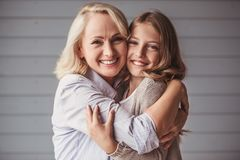 Granny and granddaughter. Beautiful granny and teenage granddaughter are hugging, looking at camera and smiling royalty free stock images