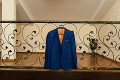 Beautiful gray groom`s suit hanging on the wardrobe. Beautiful blue groom`s jacket hanging on the wrought-iron railing Stock Image