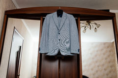 Beautiful gray groom`s suit hanging on wardrobe in the room. Beautiful gray groom`s suit hanging on the wardrobe in the room Stock Images