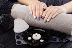 Beautiful gray manicure with towel on the white wooden table. spa Royalty Free Stock Photography