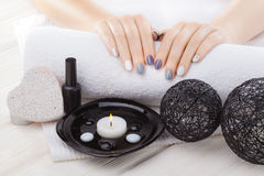 Beautiful gray manicure with towel on the white wooden table. spa Royalty Free Stock Image
