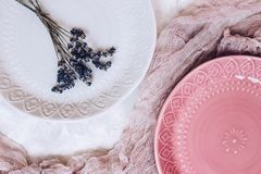 Beautiful gray and pink ceramic plates with a bouquet of lavender, pink gauze on gray concrete background. Vertical Stock Image